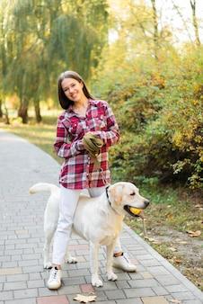 Счастливая женщина играет со своей собакой