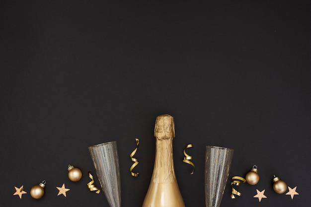 Бутылка шампанского и украшения с бокалами и копией пространства