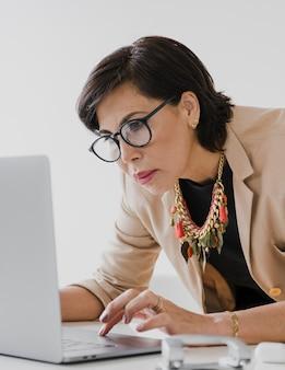 Пожилая деловая женщина работает на ноутбуке