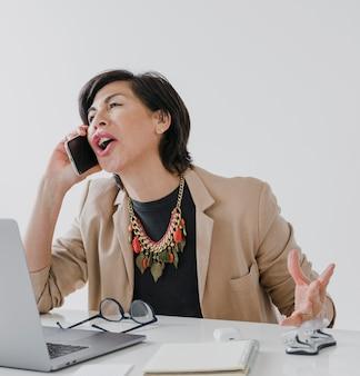 彼女のオフィスで電話で話しているネックレスを持つ年配の女性