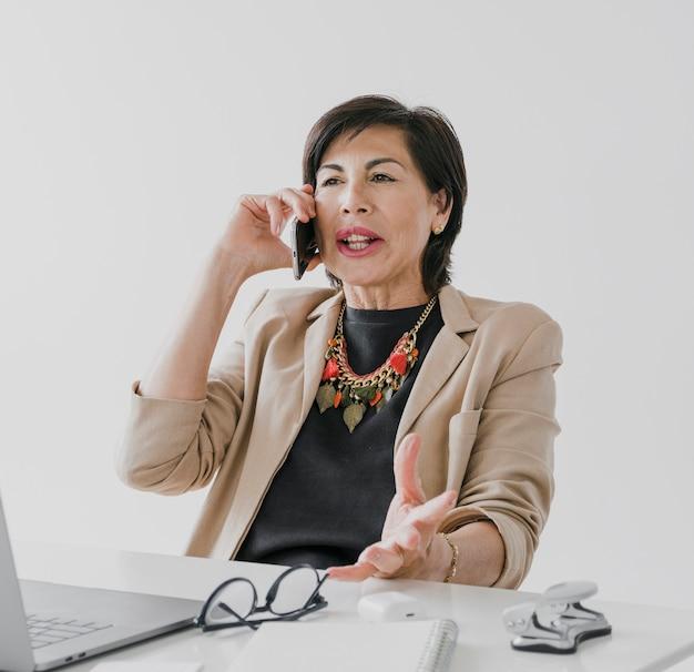 Пожилая женщина с ожерельем разговаривает по телефону