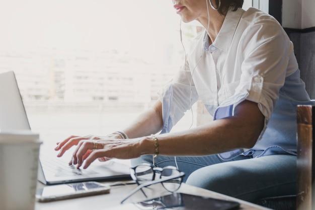 Женщина печатает на клавиатуре ноутбука