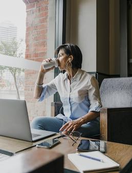 彼女のオフィスでコーヒーを飲むシニア