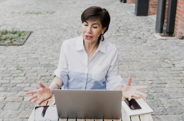 Пожилая женщина сидит на улице с ноутбуком
