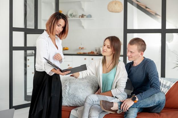 Агент по продаже недвижимости вид спереди разговаривает с мужчиной и женщиной