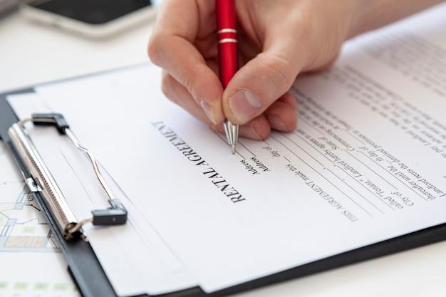 Высокий угол человек подписывает контракт на новый дом