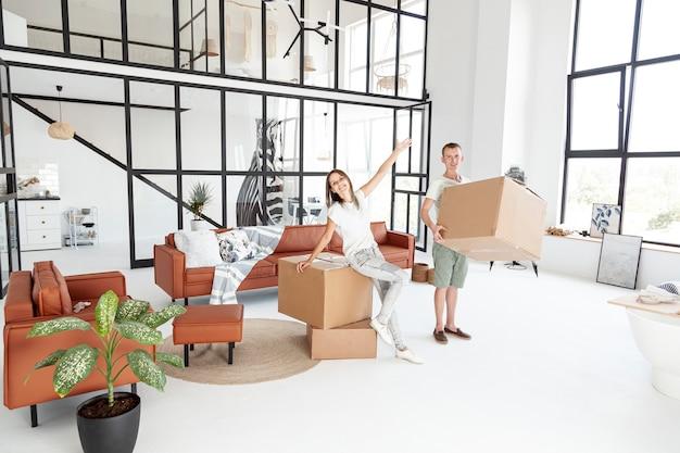新しい家に満足しているロングショットのカップル
