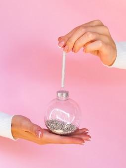 Руки держат елочный шар с блеском