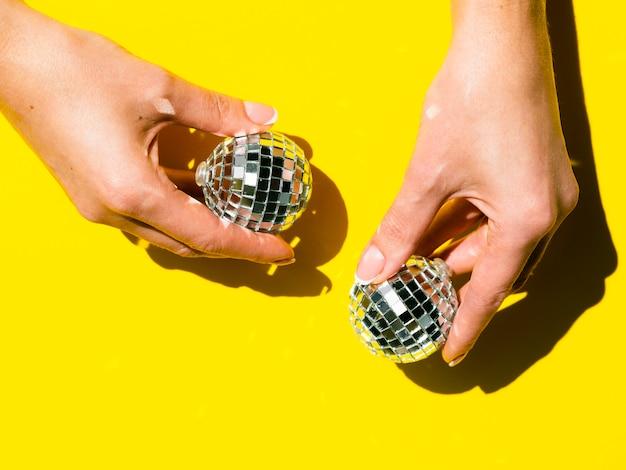 Руки держат серебряные диско-глобусы