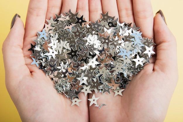 Макро руки держат серебряные звездные блестки