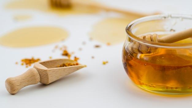 木製のスクープの横にあるおいしい蜂蜜