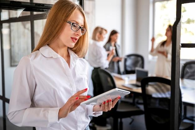 Высокий угол женский корпоративный работник с планшета