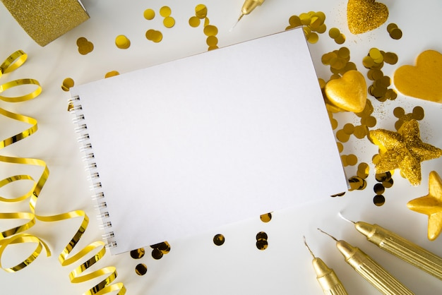 Вид сверху пустой блокнот в окружении золотых лент и блесток