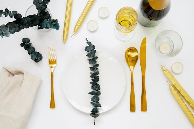Вид сверху золотые столовые приборы с листьями на тарелке