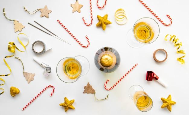 Вид сверху на расположение бокалов шампанского и конфет на новогоднюю вечеринку