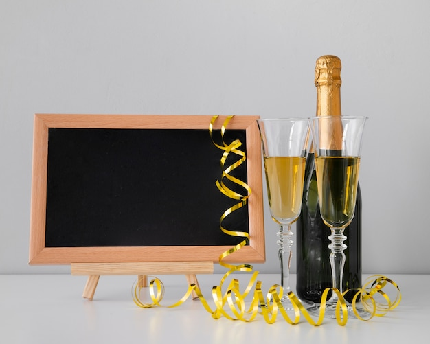 黒板のモックアップとシャンパンを備えた正面図の配置