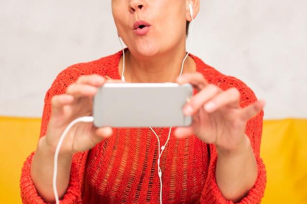 ミュージックビデオを見てクローズアップ年配の女性