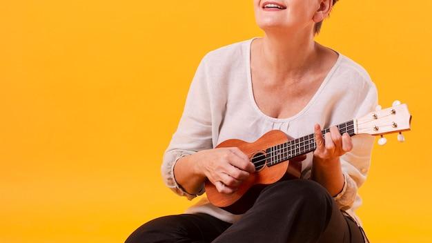Крупным планом старшая женщина играет на гитаре