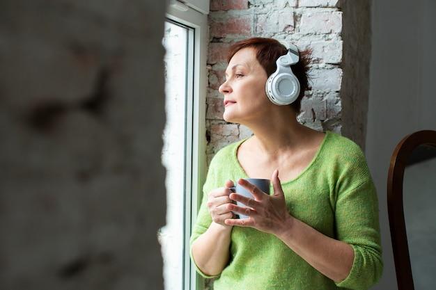 夢のような年配の女性が音楽を聴く