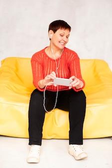 音楽を聴くソファの上の低角度のシニア女性