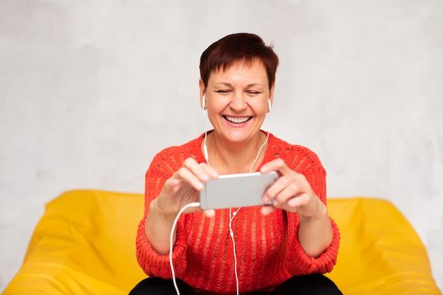 Женщина вид спереди слушает музыку и смотрит на телефон