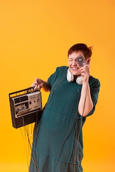 カセットプレーヤーを保持している面白い年配の女性