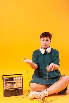 カセットテープを保持しているフルショット年配の女性