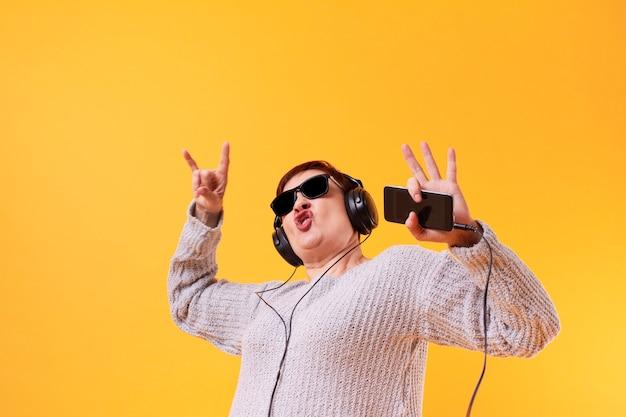 面白い年配の女性がロック音楽を聴く