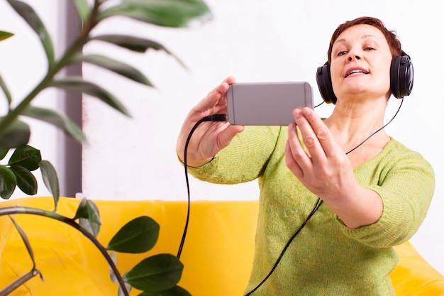 Женщина прослушивания музыки и принимая селфи