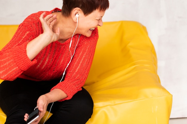 ソファの上に立地し、音楽を聴く女性