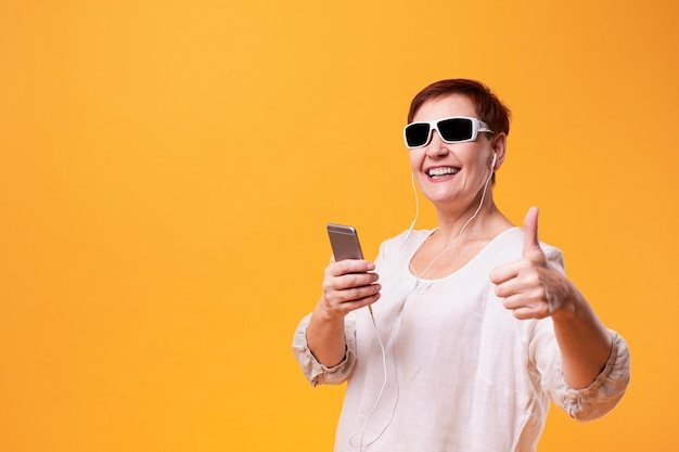 Старшая женщина держа телефон и показывая одобренный знак