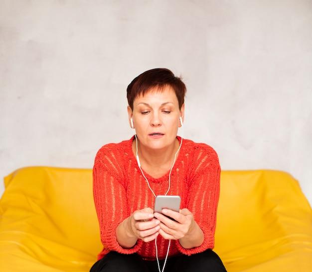 Вид спереди женщина сидит на диване и слушает музыку
