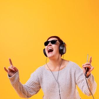 Старшая женщина слушает рок-музыку