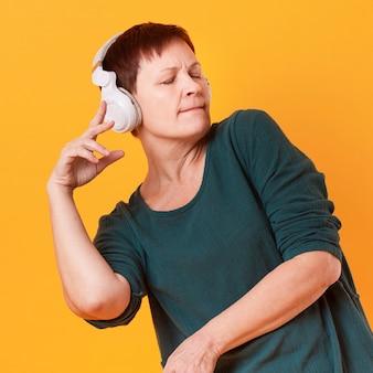 ミディアムショットの年配の女性のダンスと音楽を聴く