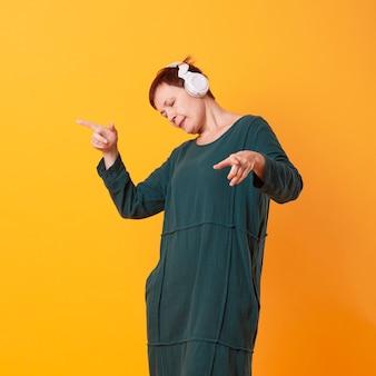 Портрет пожилой женщины танцует и слушает музыку