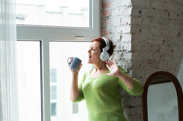 Женщина слушает музыку и поет