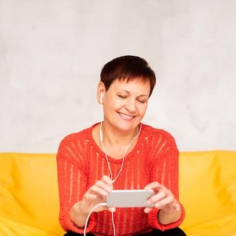 フロントビュー年配の女性が音楽を聴く