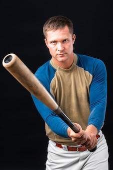 野球のバットを押しながらポーズの男