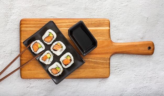 Плоские лежалки с суши роллами с соевым соусом