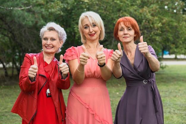 Зрелая женщина с большими пальцами руки вверх