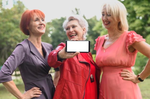 Женщина с друзьями держит мобильный телефон