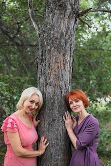 木の横にある美しい年配の女性