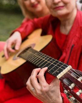 Крупным планом пожилая женщина играет на гитаре