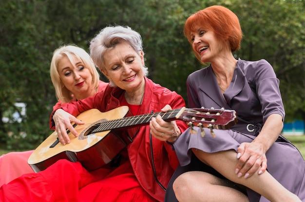 Зрелая женщина играет на гитаре с друзьями