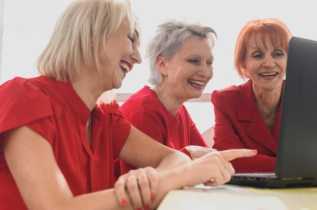 ラップトップ上で閲覧してクローズアップ年配の女性