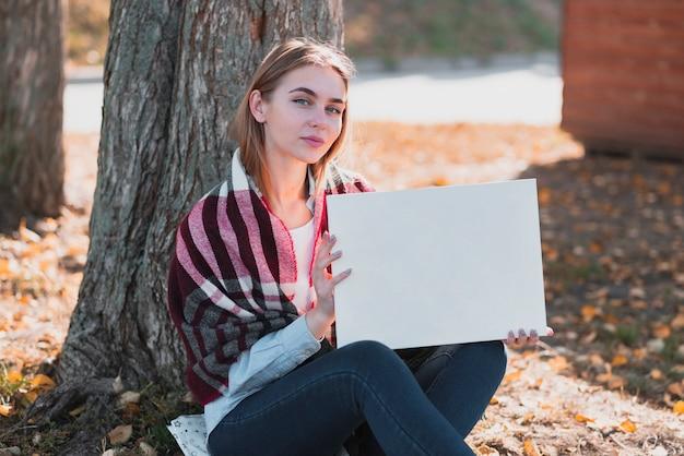 Красивая женщина держит рамку с макетом