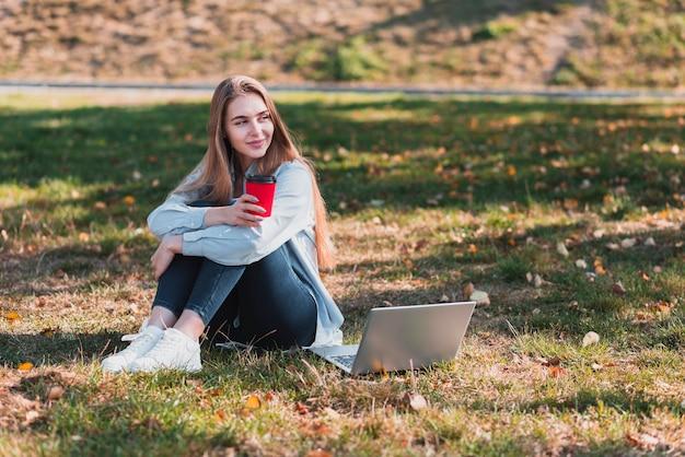 自然の中でカップを保持している若い女の子