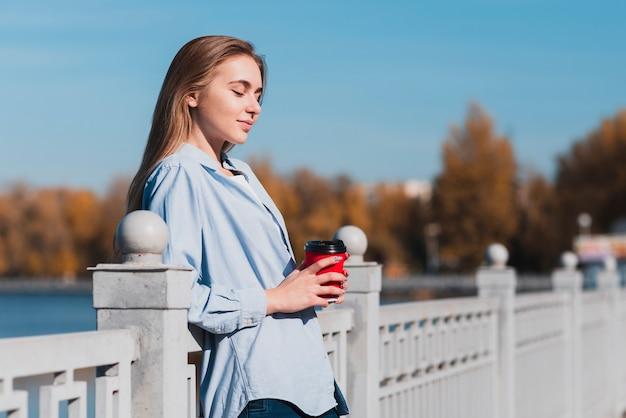 手すりで休んで、コーヒーカップを保持している金髪の女性