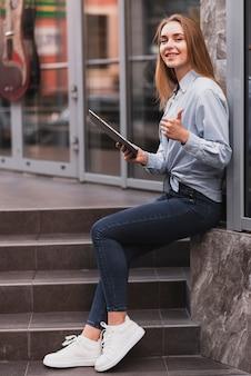 Боковой вид блондинка девушка держит планшет