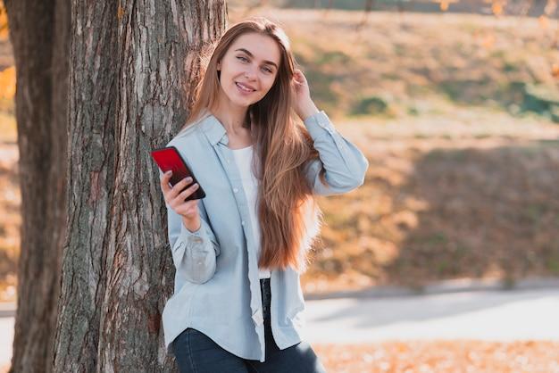 携帯電話を保持しているカジュアルな服装の女性
